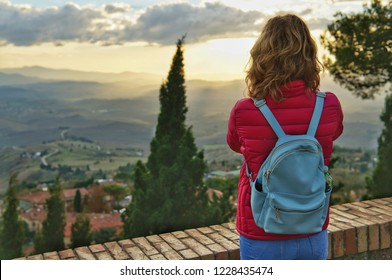 Young girl photographer takes pictures of the hills of Tuscany