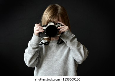 Young girl photographer taking photograph with camera film or digital