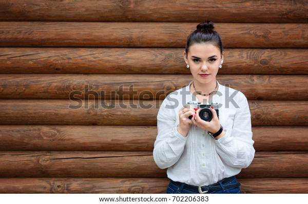 Young girl photographer in white blouse and blue jeans makes photo on old retro film camera. Wooden background