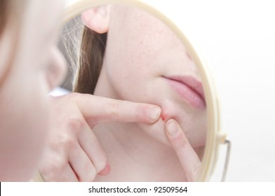 young girl picking at face in mirror