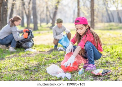 Young girl picking up trash in the park. Volunteer concept