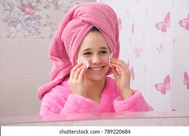 Young girl in pink bathrobe cleaning his face with cotton pads in the bathroom looking to mirror