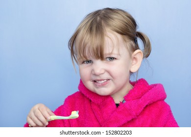 A young girl in a pink dressing gown against a light blue background. She's cleaning her teeth and smiling at the camera.