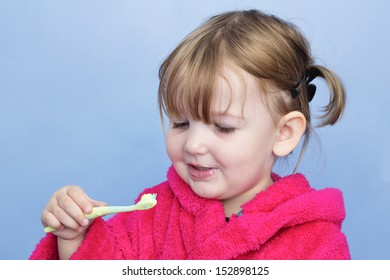 A young girl in a pink dressing gown against a light blue background. She's cleaning her teeth and has stopped to smile at the brush.