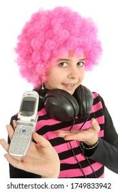 Jeune fille avec des cheveux roses et des écouteurs montre son vieux téléphone portable, isolée sur fond blanc