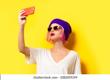 Young girl with pink hair in purple hat making selfie by mobile phone on yellow background