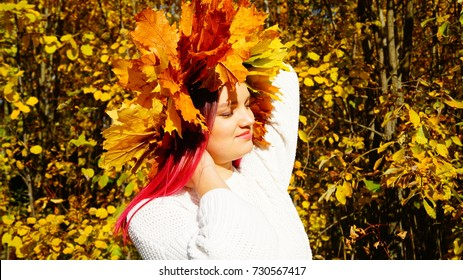 Young girl with pink hair and a wreath of leaves. Golden trees in the park. Autumn.