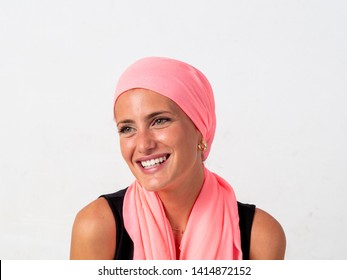 Young girl with pink handkerchief on her head and white background, fighting cancer