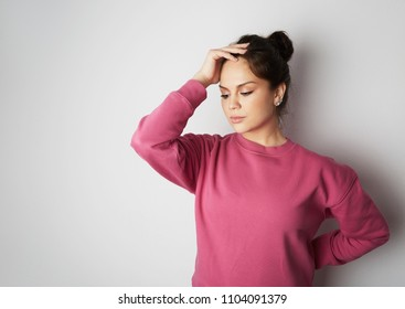 Young girl in pink hoody with a severe headache with the hands in the head over white empty wall on background. Beauty and healthcare concept