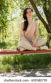 The young girl in a pink jacket sits on bench in pose of the yogi, in the park