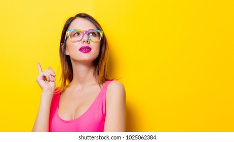 Young girl in pink one-piece swimming suit with eyeglasses on yellow background