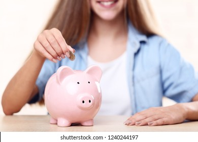 Young girl with pink piggybank sitting at table