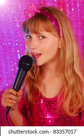 young girl in pink shiny dress singing with microphone on the stage