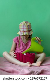 young girl in pink shirt and hat holding garden and flower pot on green background