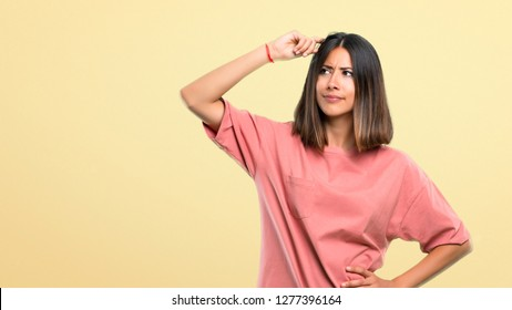 Young girl with pink shirt having doubts and with confuse face expression while scratching head on yellow background