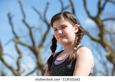 Young girl with plaits looking to camera with attitude, dressed in sporty clothes in in a park in Winchester, Hampshire, UK