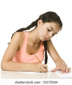 Young girl with plaits writes with concentration