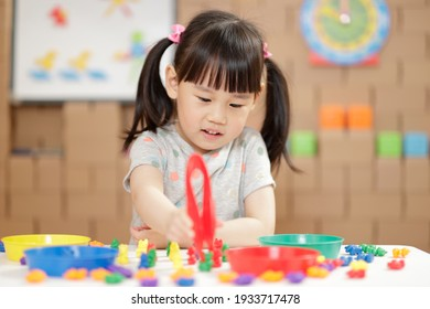 young girl play math and color sorting fine motor skill game for