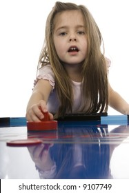Young girl playing air hockey isolated on white