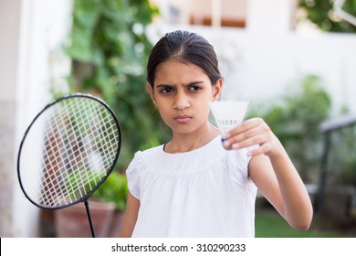 young girl playing badminton outdoors holding a racket and a shuttle cock in a pose to serve