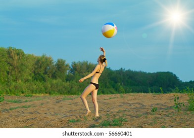 Young girl playing with a ball on the sandy beach