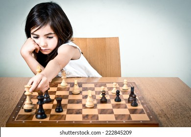 Young girl playing chess.