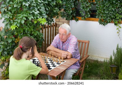 Young girl playing chess with her grandfather in garden