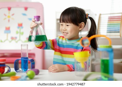 young girl playing color sorting and fine motor skill toy at hom