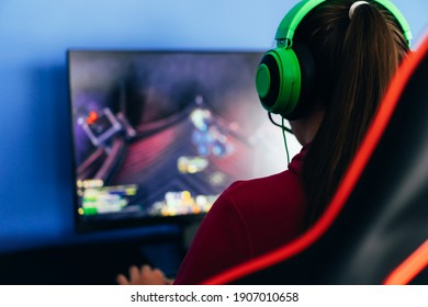 A young girl playing a computer game on professional armchair against monitor in green headphones, live stream, esports.