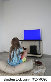 Young girl playing in the console in front of the TV
