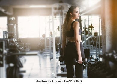 Young girl playing dumbbell to exercise in fitness.Slim girl lifts heavy dumbbell while training in the gym. Sports concept fat burning and a healthy lifestyle.