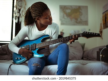 Young girl playing electric guitar in her bedroom