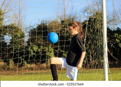 Young girl playing English football at a countryside sports field.UK