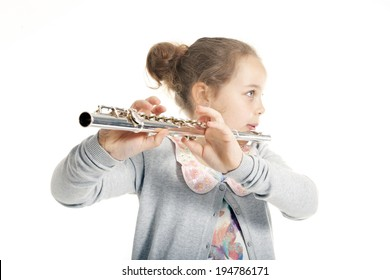 young girl playing flute against white background in studio