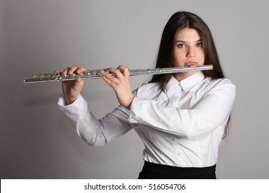 Young girl playing flute, on gray background