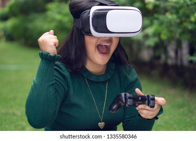 Young girl playing games with a virtual reality glasses