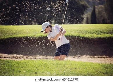 young girl playing golf on a sunny day moving sand in the banker