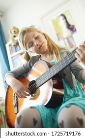Young girl playing guitar in bedroom