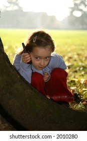 Young girl playing hide and seek holding a mobile phone