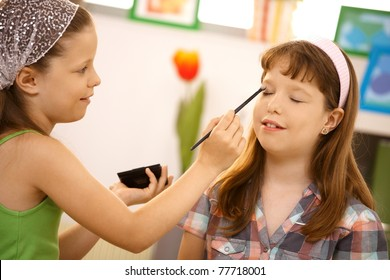 Young girl playing at home, putting makeup on friend, smiling.?