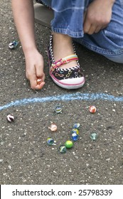 Young girl playing marbles within a chalk ring