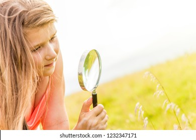 Young girl playing in a meadow with a magnifier