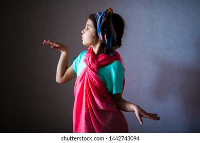 Young girl playing with mom's clothes. She changes into a national costume. Indian, Thailand and Asian style. Child's fashion perfomance.