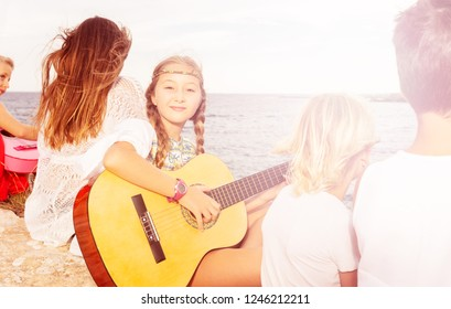 Young girl playing music on acoustic guitar