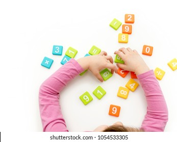 Young girl playing with numbers on white table. Studio isolated. Top view