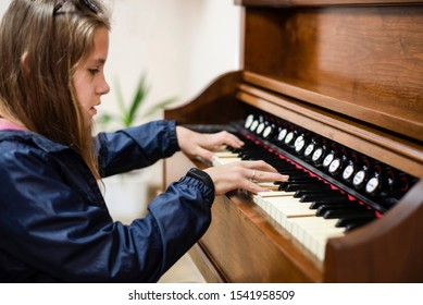 Young girl playing an old piano known tune. Girl dressed in a jacket because in the music class is cold, the heating system is not working yet. The girl's hands are gracefully lie down on the keys