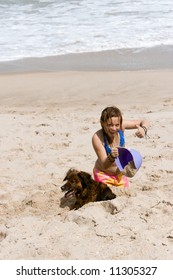 Young girl playing on the beach in the sand with a purple bucket and her dog
