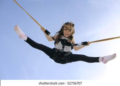 Young girl playing on bungee trampoline