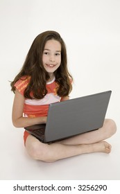 Young girl playing on a laptop computer on a white background