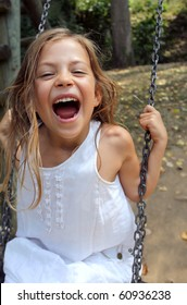 Young girl playing on a swing in a park and screaming with delight